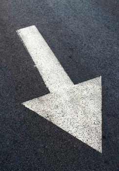 White arrow on asphalt road, traffic sign