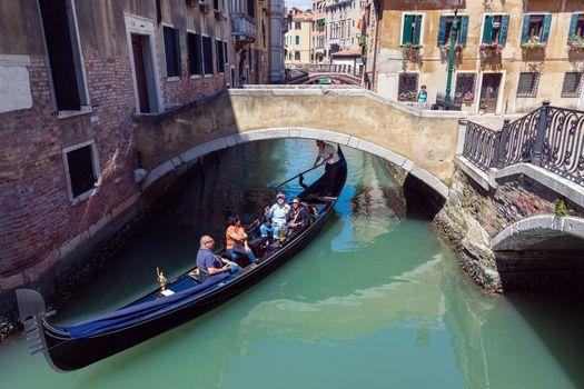 VENICE, ITALY - MAY 27, 2015: Tourists on a gondola on sunny day in Venice, Italy.