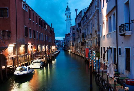 Tranquil canal with moored boats early in the morning in Venice, Italy