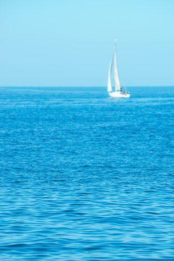 Blue summer seascape with distant yacht out of focus