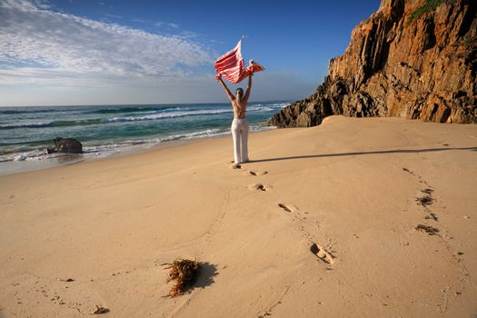 A woman walks along the beach, travel, health and wellbeing
