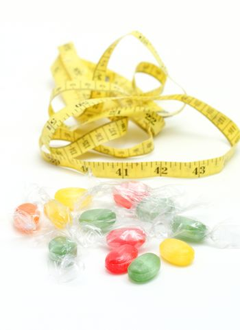 picture of a the colored fruit taste candies. and tape measure .sweet food concept