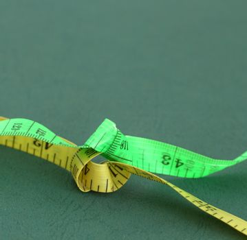picture of a yellow and green tape measure on green background