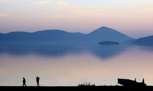 pisture of a men picturing lake prespa in macedonia on sunset