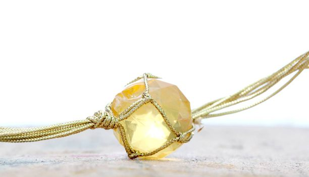 picture of a necklace with cheap plastic gems with golden colored rope