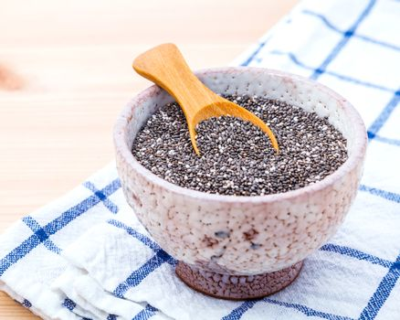 Nutritious chia seeds in ceramic bowl on wooden table for diet f