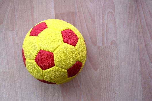 picture of a Red and yellow Soccer Ball on a wooden background