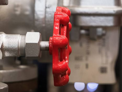 Red valve handle in industrial environment. Shallow depth of field with only the handle in focus.