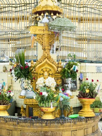 Buddha image decorated with flowers at the Botahtaung Pagoda in Yangon, Myanmar