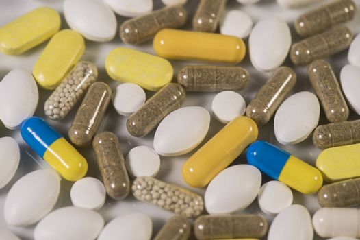 Colored pills, tablets and capsules on a white background