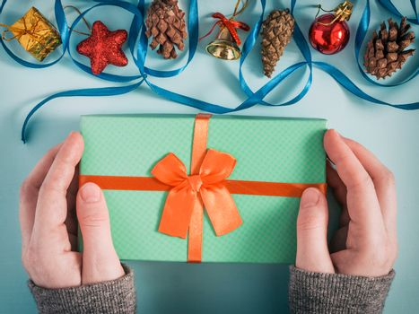 Female hands hold christmas gift box above azure table. Top view or flat lay. Toned image