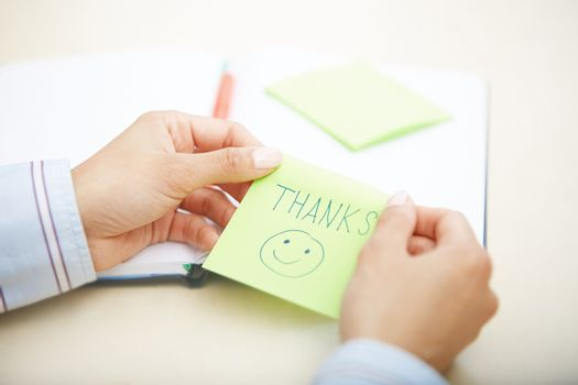 Hands of woman holding sticky note with Thanks text