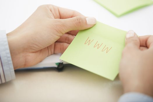Hands holding sticky note with internet address. Close-up view