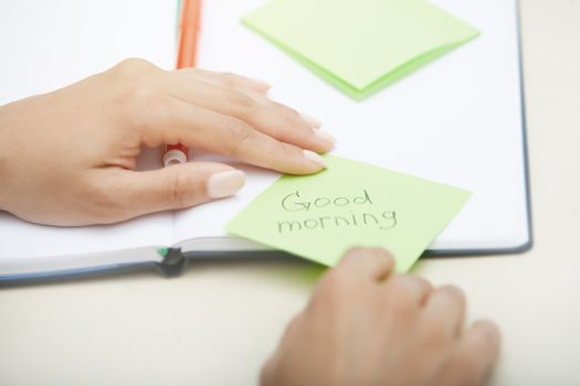 Hands holding sticky note with Good morning text