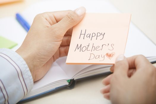 Hands holding sticky note with Happy mothers day text