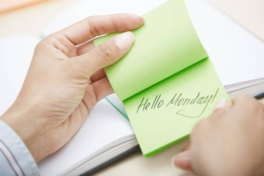 Hands holding sticky note with Hello Monday text