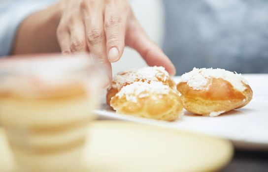 Woman taking eclairs from a plate