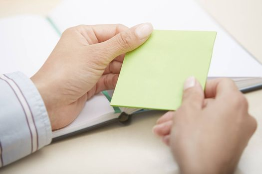 Hands holding green sticky note with empty space