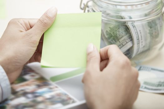Hands of businessperson holding adhesive note with empty space