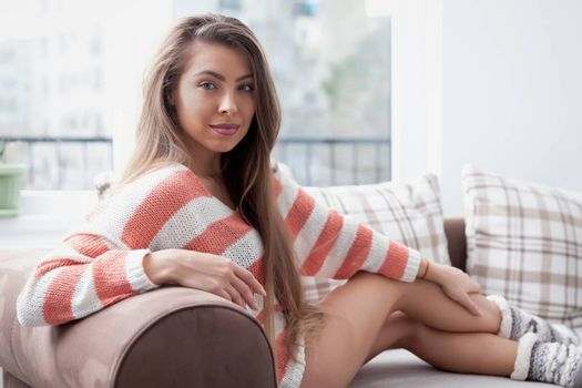 Lovely young woman wearing a large sweater and winter socks.