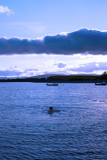 man swimming in a quiet bay near kenmare on the wild atlantic way ireland with a cold blue sunset