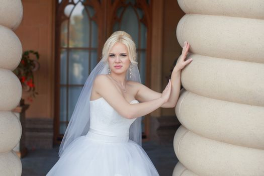 The blonde bride standing at the wall, posing in the photo
