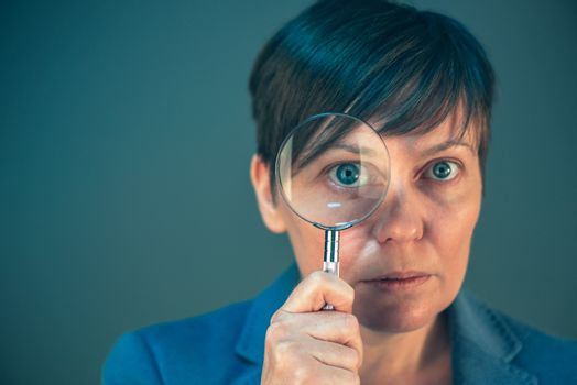 Beautiful businesswoman looking through magnifying glass