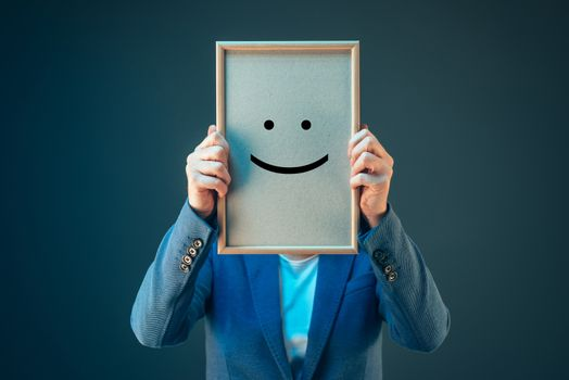 Businesswoman is optimistic, holding smiley emoticon over face