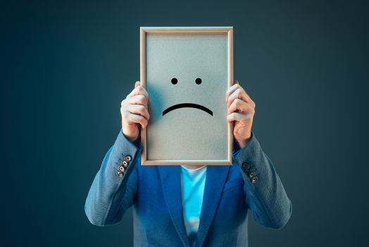 Businesswoman is pessimistic, holding smiley emoticon over face