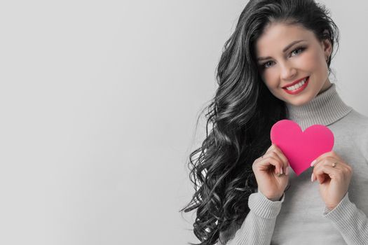 Portrait of a pretty woman holding a paper heart against gray background