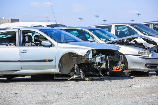 several cars in a scrap yard available for spare parts