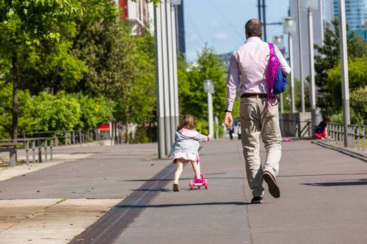 A father walking and young happy daughter skatingalong the street in the afternoon.