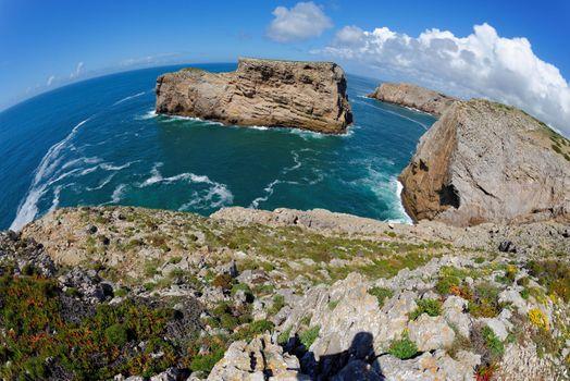 Fisheye view of scenic rocks in the ocean near Cabo de Sao Vicente Cape in the Algarve, Portugal