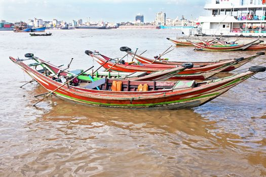 Traditional wooden fisher boats in the harbor from Yangon in Mya