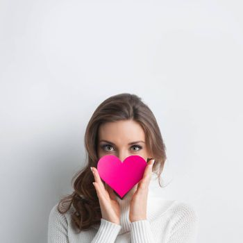 Beautiful woman holding Valentines day paper heart card