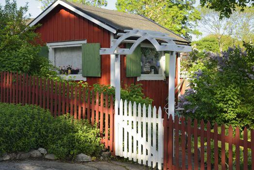 Idyllic red cottage in botanical garden.
