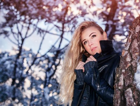 Portrait of beautiful blond woman standing near tree in the winter park, fashionable clothing, gorgeous model posing outdoors