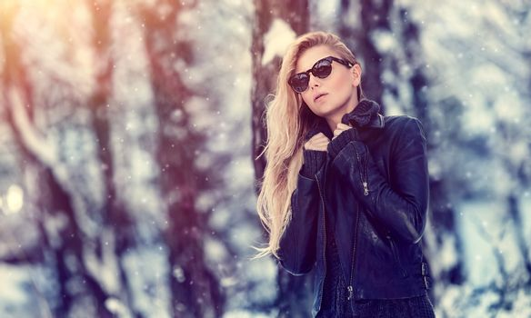 Portrait of cute blond female wearing stylish sunglasses and leather jacket in winter park, cool street fashion