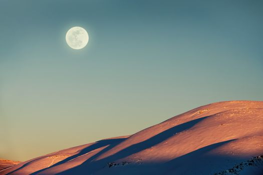 Beautiful winter landscape, amazing view on the moon by day over mountains covered with snow, stunning wintertime nature