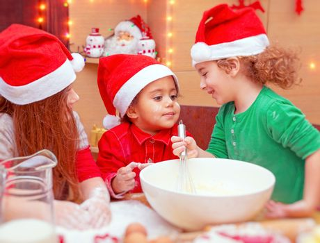 Three kids making Christmas cookies, cute little cooks wearing santa hats doing traditional gingerbread, happy winter holidays