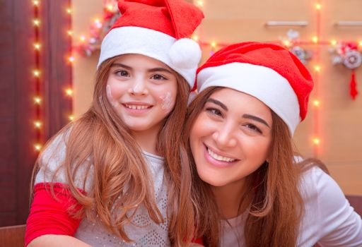 Closeup portrait of mother with cute little daughter wearing Santa hat baking on the kitchen at home, enjoying traditional Christmas preparation