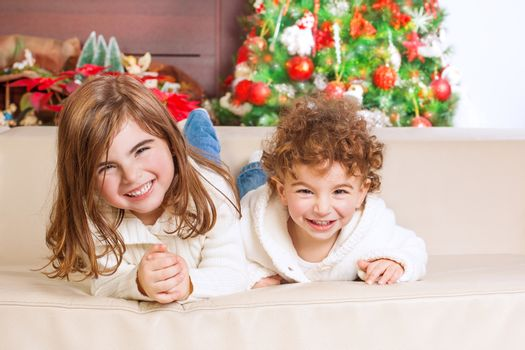 Two happy kids lying down on sofa under beautiful decorated Christmas tree and laughing, cheerful family spending winter holidays at home