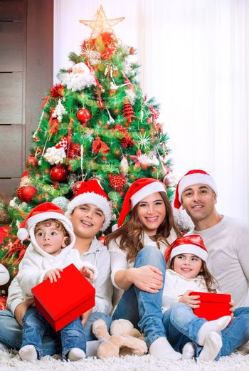 Portrait of big happy family wearing Santa hat sitting near beautiful decorated Christmas tree, with fun spending winter holidays together at home