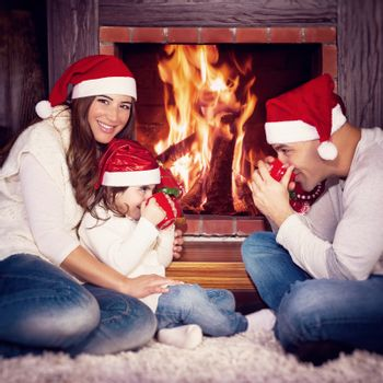 Lovely family sitting near fireplace and drinking tea, spending Christmas eve at home, happy winter holidays