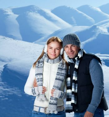 Happy active couple spending winter holidays in the mountains covered with snow, young family with pleasure travel together