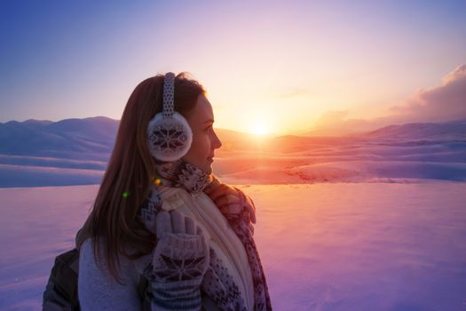 Side view of beautiful girl enjoying amazing view on sunset, spending winter holidays in the snowy mountains, active lifestyle of young people