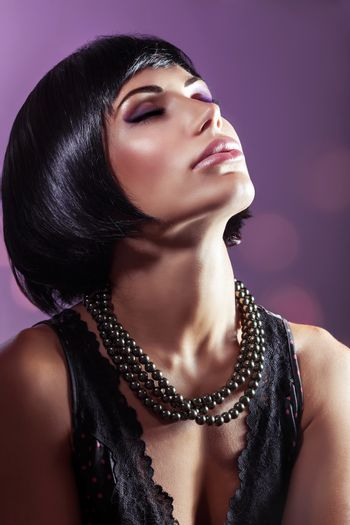 Sensual portrait of a beautiful woman with closed eyes over purple background, gorgeous lady with perfect hairstyle and makeup wearing black pearls beads, fashion look
