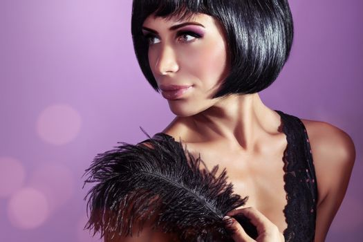 Portrait of an attractive stylish model posing with black feather over purple background, stylish bob haircut and colorful makeup, retro fashion look