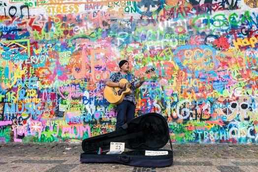 PRAGUE, CZECH REPUBLIC - JUNE 27, 2016: Street artist playing guitar at the famous Lennon graffiti wall in old town of Prague, Czech Republic