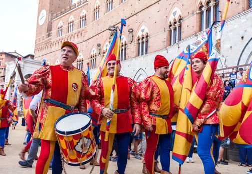 SIENA, ITALY - JUNE 29, 2016: Men in historical colorful costumes ready to celebrate and parade at traditional Palio horse race in Siena, Italy